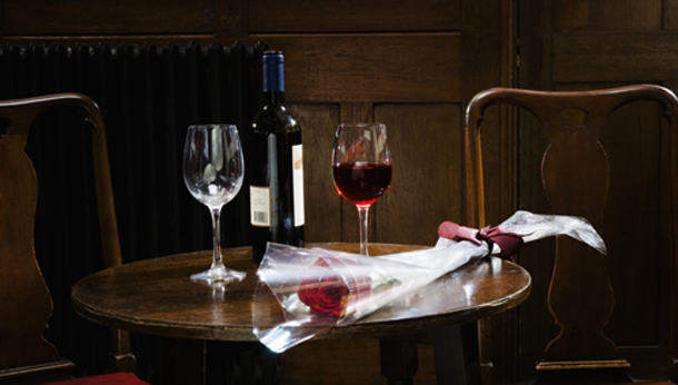 Rose, glasses and bottle of wine on table in wine bar