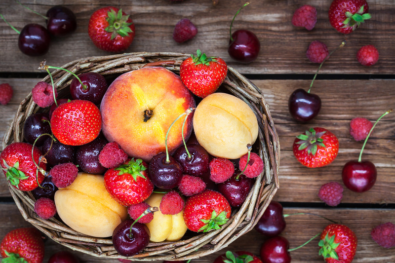 Fresh ripe summer berries and fruits (peaches, apricots, cherry, strawberry and raspberry) in wicker basket, top view